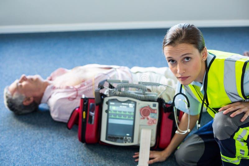 Person med paramedicinsk utbildning som använder en yttre defibrillator under cardiopulmonary återuppväckande arkivfoto