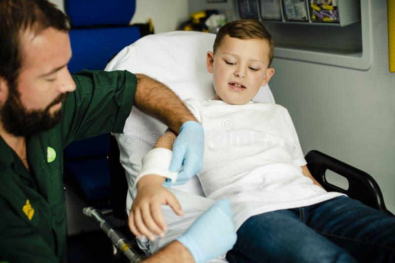 Person med paramedicinsk utbildning som ger en första hjälpen till en ung pojke i en ambulans arkivfoton