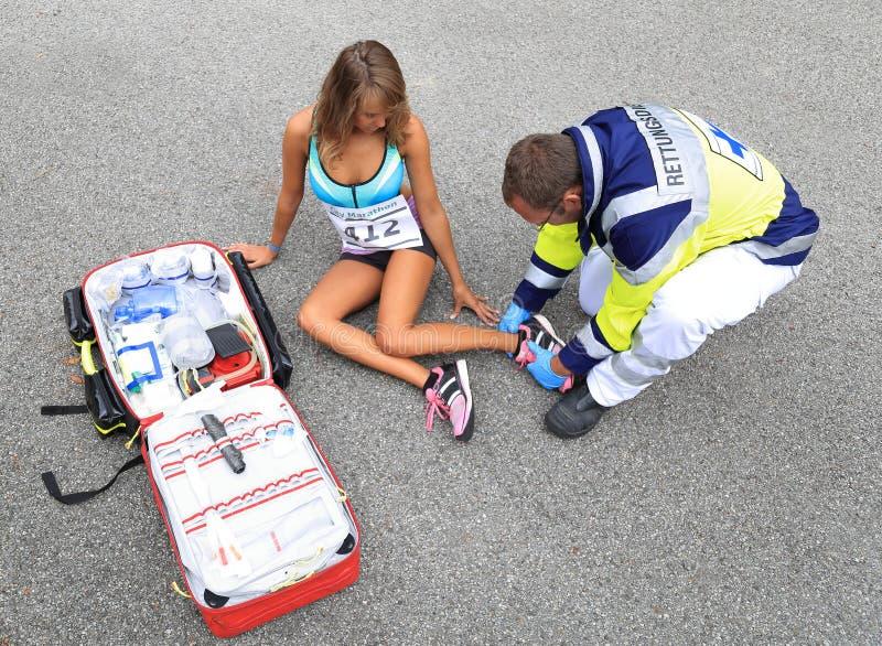 Person med paramedicinsk utbildning som hjälper en kvinnlig löpare med ankelolycka fotografering för bildbyråer