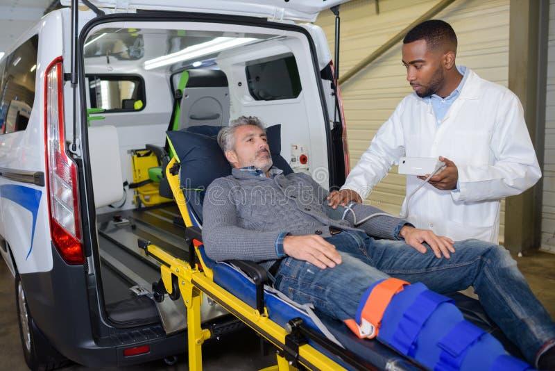 Person med paramedicinsk utbildning som tar tålmodigt blodtryck för ` s arkivbilder