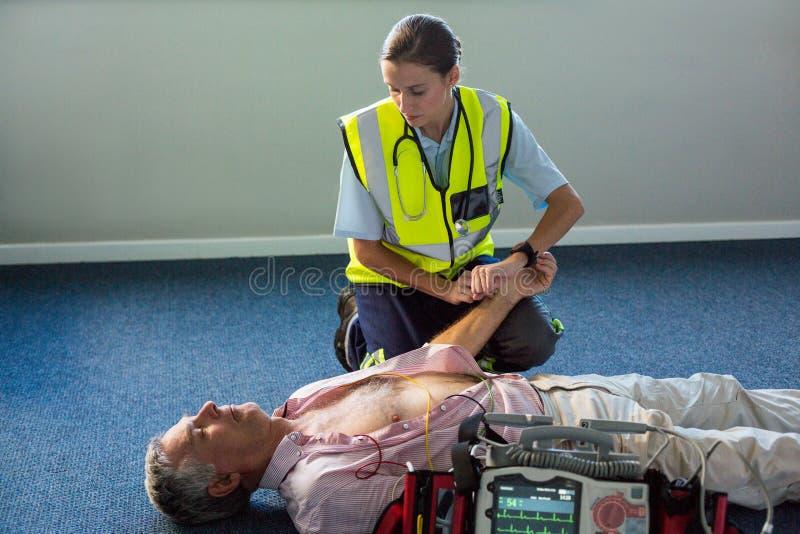 Person med paramedicinsk utbildning som undersöker en patient under cardiopulmonary återuppväckande royaltyfri fotografi