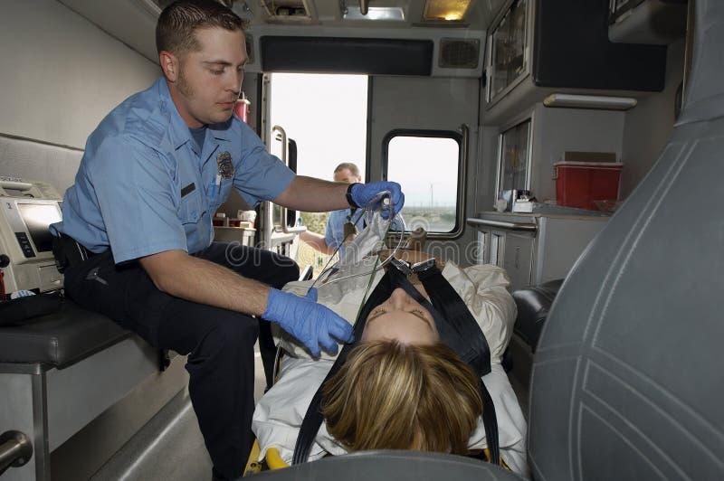 Person med paramedicinsk utbildningWith Victim In ambulans fotografering för bildbyråer