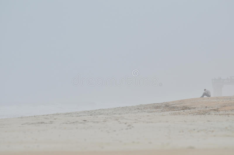 Person on misty beach royalty free stock photo
