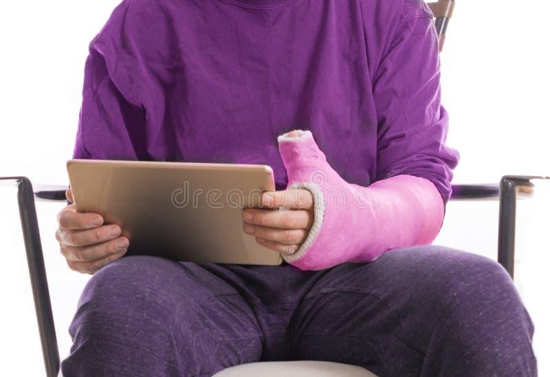 Person mit dem Arm warf unter Verwendung einer zugänglichen Tablette stockfoto