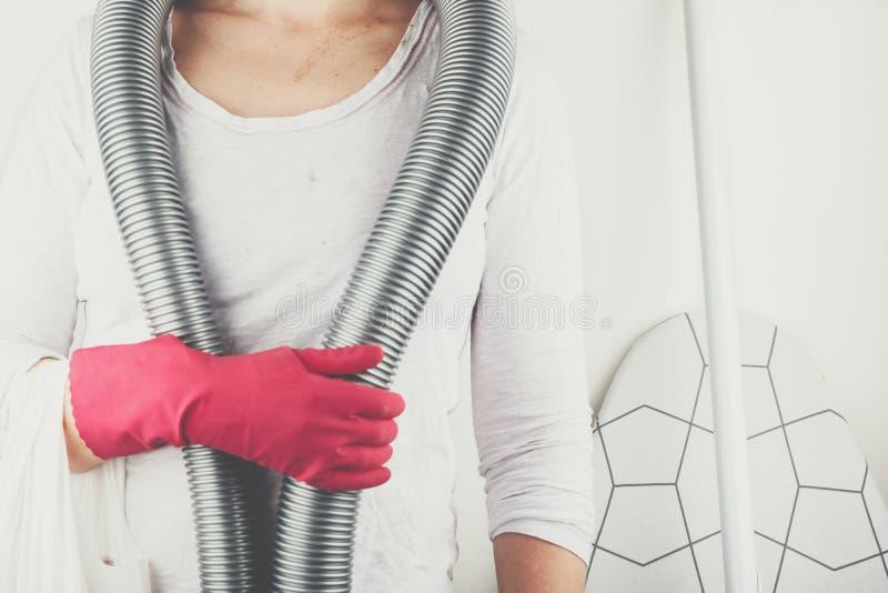 Person mit rotem Gummihandschuh und ein Staubsauger um Hals lizenzfreie stockfotografie