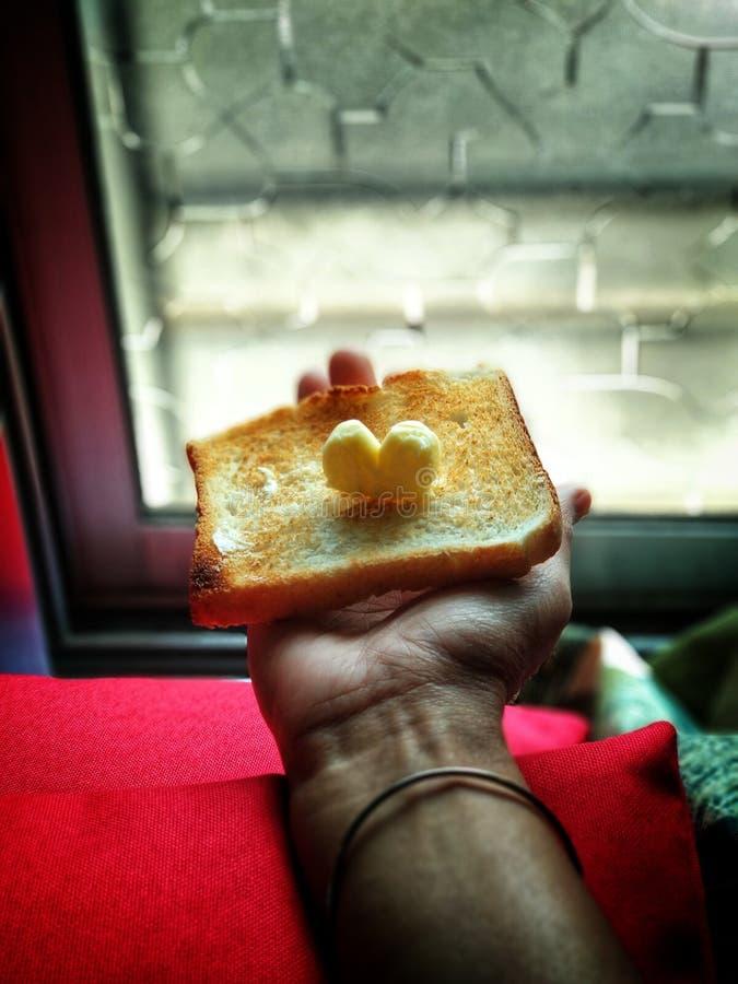 Person mit Toast oben mit Butter lizenzfreies stockbild