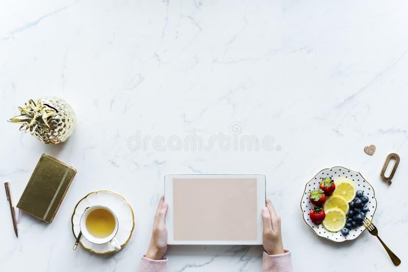 Person mit weißem Tablet-Computer neben Teacup und Saucer von Blaubeeren stockbild