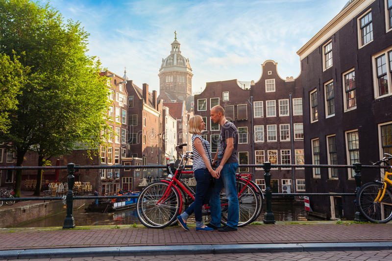 Person mit zwei Liebhabern in Amsterdam auf einem Hintergrund des mehrfarbigen Hauses in den niederländischen Artstand- und -grif stockbilder