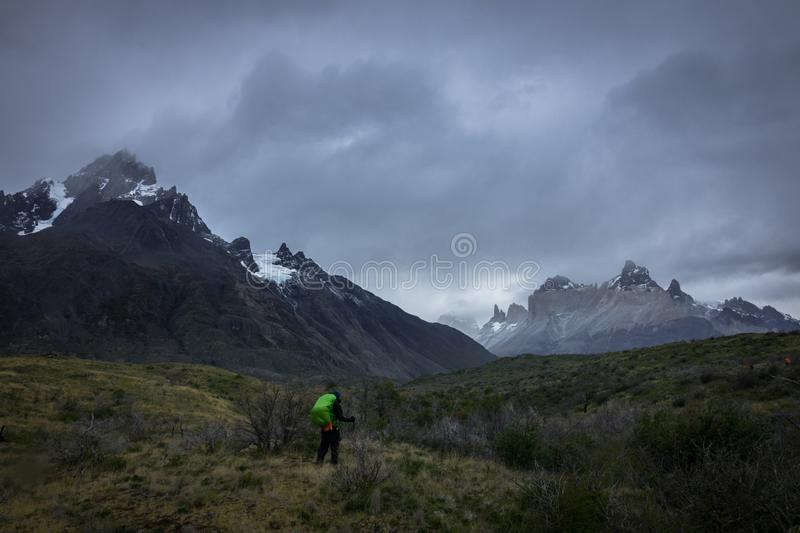 A person observing an immense landscape of great mountains. And snowy peaks, surrounded by small bushes, some green and others dry. Torres del Payne, Patagonia stock images