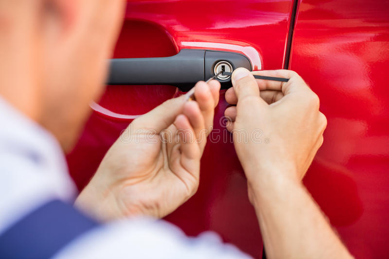 Person Opening Car Door With Lockpicker. Close-up Of Person`s Hand Opening Car Door With Lockpicker stock photos
