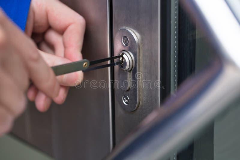 Person Opening Door With Lockpicker stock photo