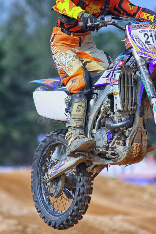 Person in Orange and Yellow Fox Motorcycle Suit Riding a Purple White Gray and Black Dirt Motorcycle Outdoors during Daytime royalty free stock photography