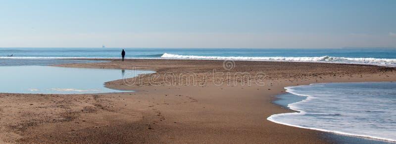 Person på liten sandbar var Stilla havet och det Santa Clara River mötet på surfarerund kullestranden i Ventura California USA royaltyfri foto