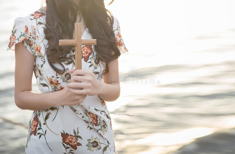 Person palm hands to hold holy cross, crucifix to worship. stock images