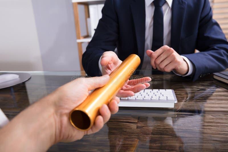 Person Passing Baton To Businessperson fotografía de archivo