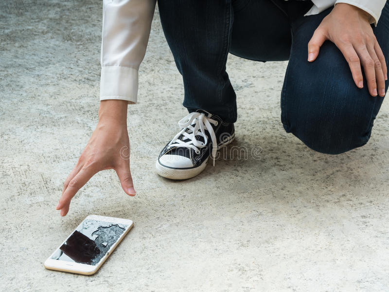 Person Picking Broken Smart Phone of Ground. Person Picking Broken Smart Phone (Cracked Screen) of the Ground royalty free stock images