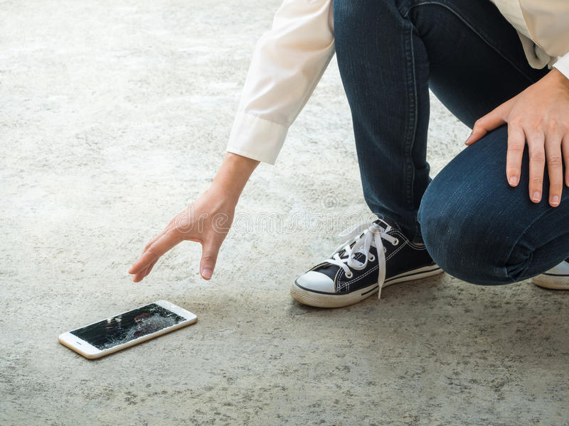 Person Picking Broken Smart Phone of Ground. Person Picking Broken Smart Phone (Cracked Screen) of the Ground stock photography