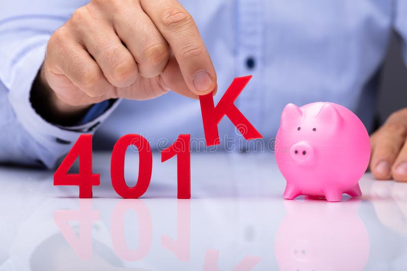 Person Picking K Alphabet From 401k Pension Plan stock photo