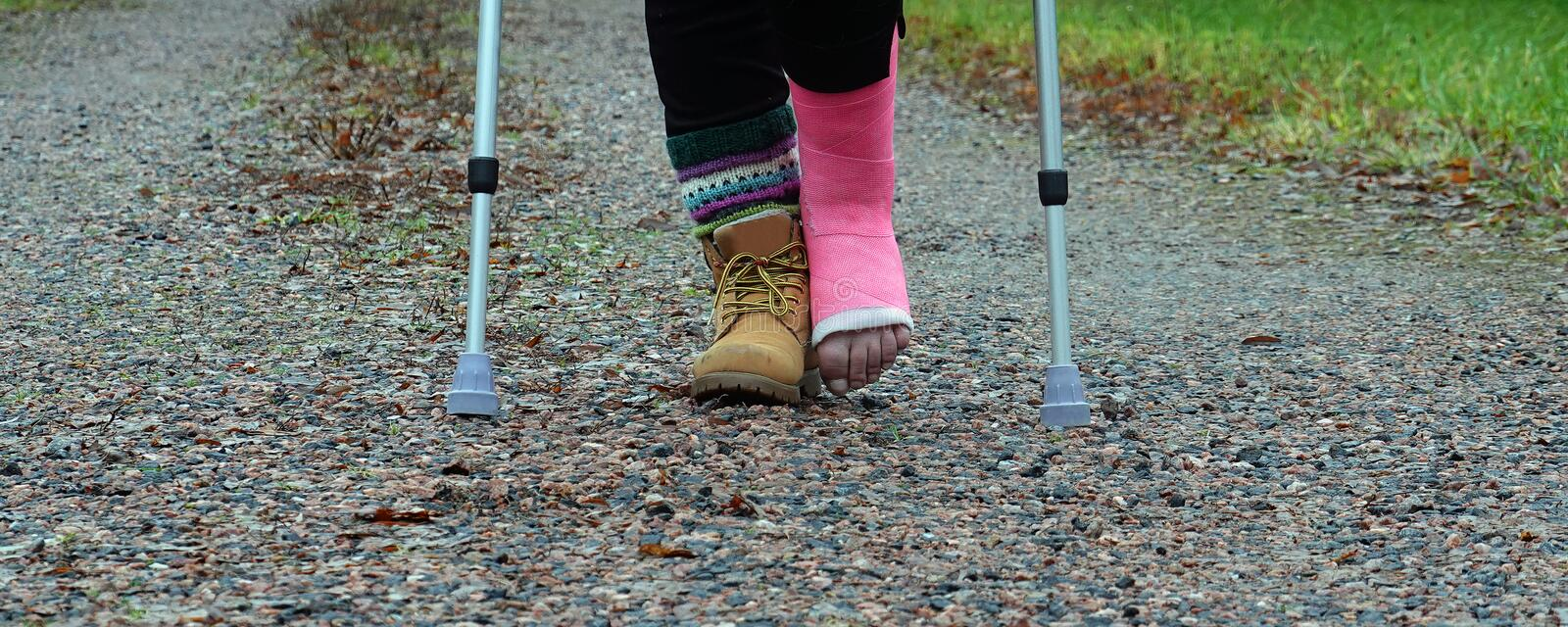 Person with pink fiberglass cast and crutches. Outdoors stock photos