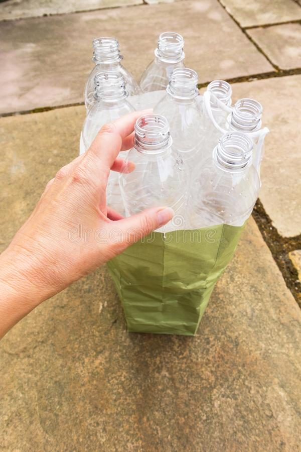 Plastic drinks bottles in a paper carrier bag. Person placing an empty plastic drinks bottle in a paper carrier bag ready for collection stock images