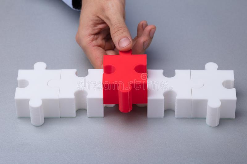 Person Placing Red Jigsaw Puzzle immagine stock