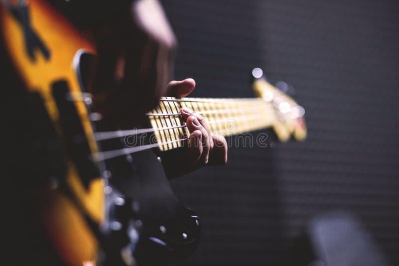 Person Playing Sun Burst Electric Bass Guitar In Bokeh Photography Free Public Domain Cc0 Image