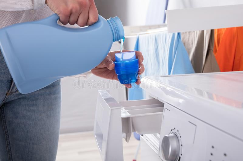 Person Pouring Detergent In Lid image stock