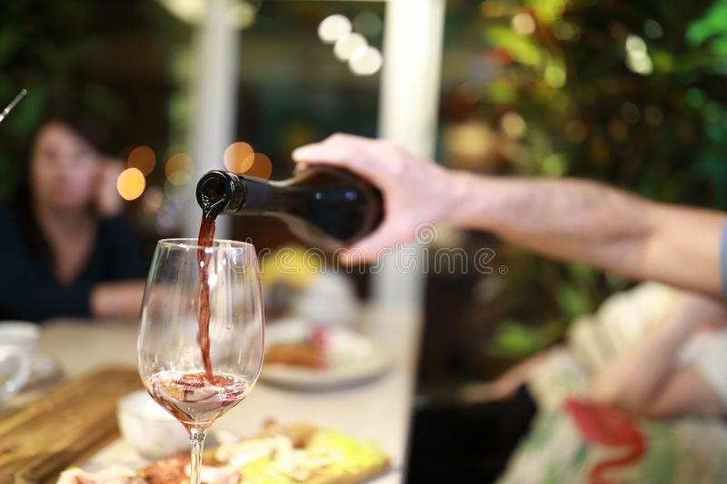 Person pouring red wine royalty free stock image