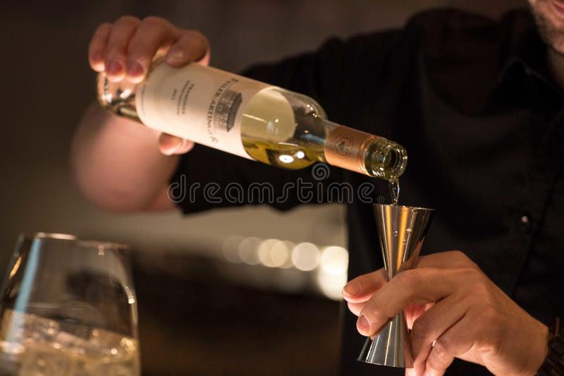 Person Pouring Wine on Grey Jigger stock images