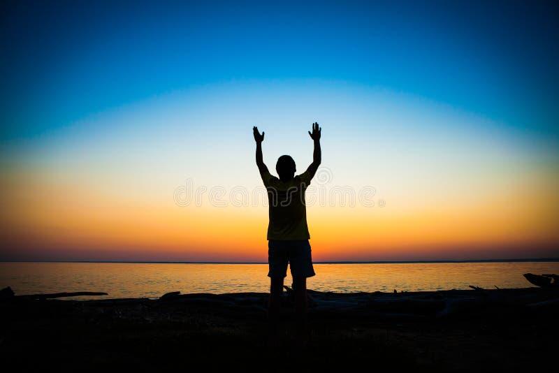 Person Praying en la puesta del sol fotografía de archivo