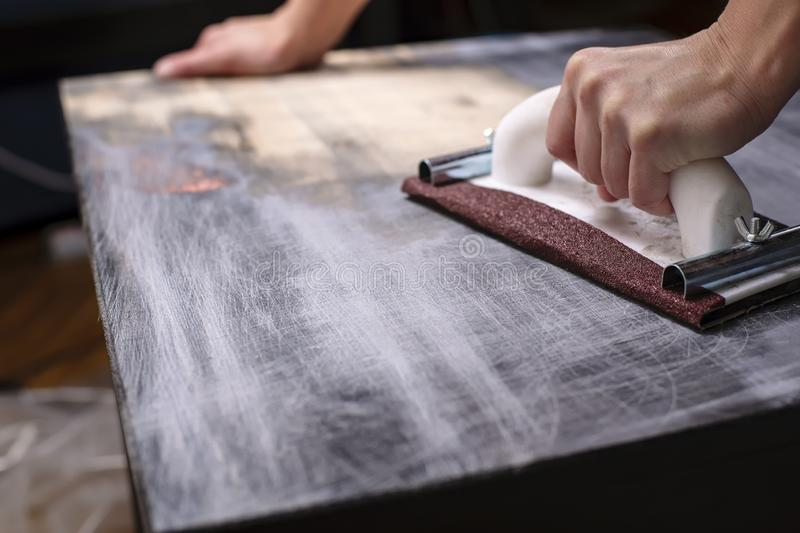 Person prepares the surface for painting and sanding by hands an old wooden black table stock photo