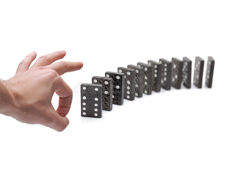 Person pushing domino blocks. Isolated against white background stock photo