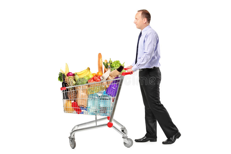 Person pushing a shopping cart full with groceries. On white background stock photography