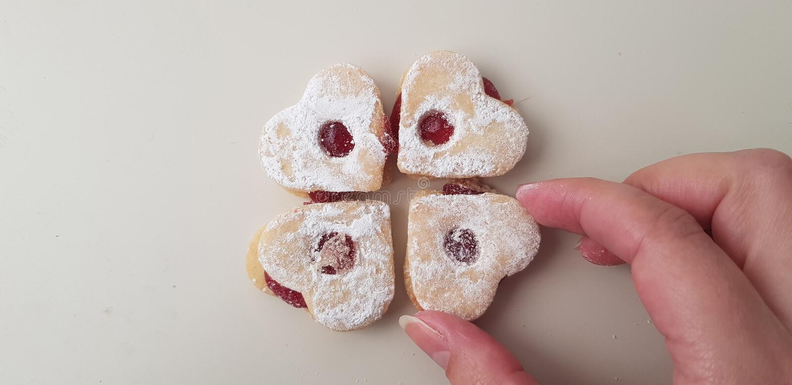 A person and puts a cookie near three more cookies on white table royalty free stock photo