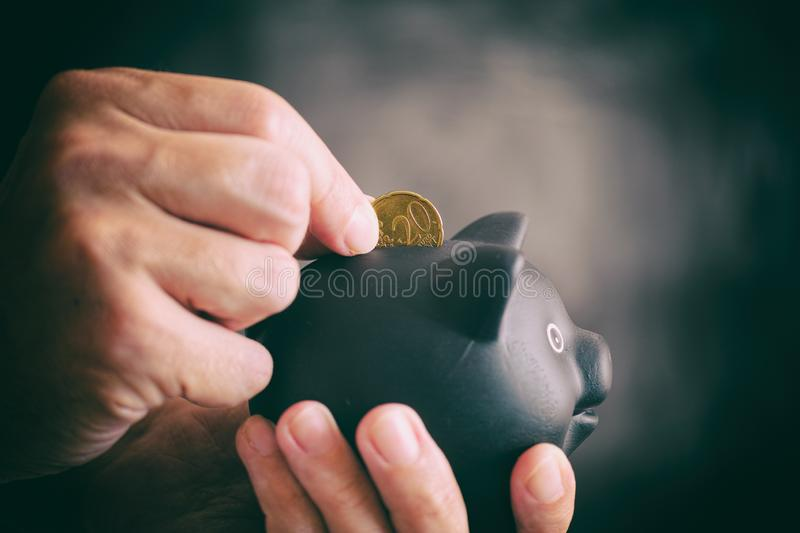 Person putting 20 euro cent coin into black piggy bank against black background. Close up royalty free stock image
