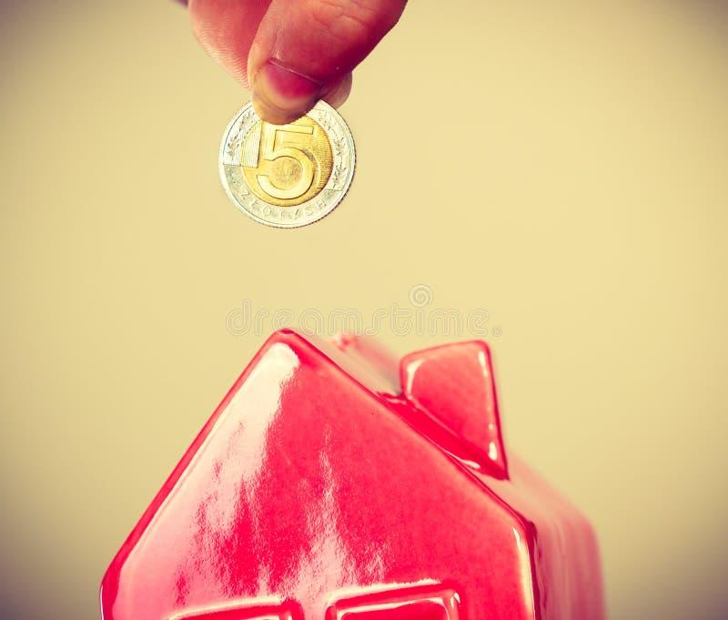 Person putting money into house piggybank stock image