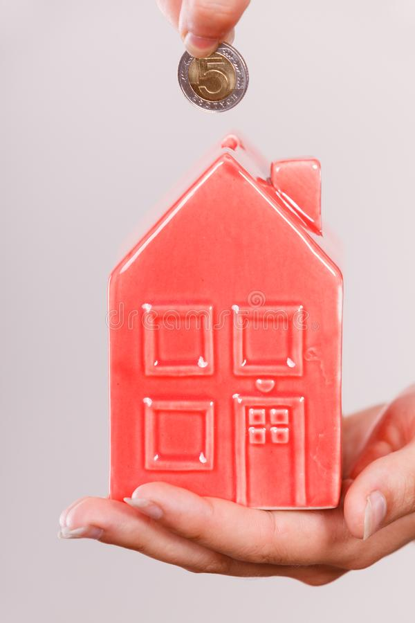 Person putting money into house piggybank royalty free stock image