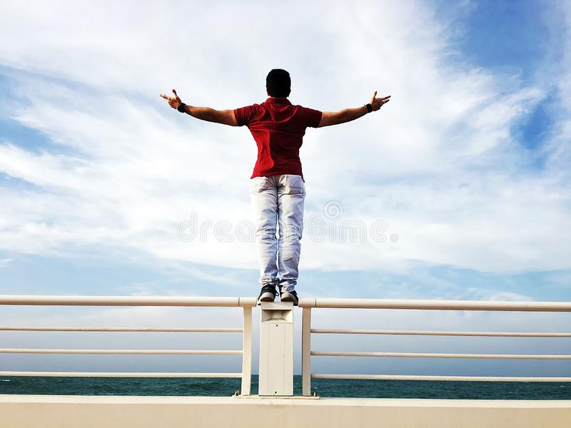 Person Raising Hands Mid-air Sidewards While Standing on Gray Steel Railings stock photos