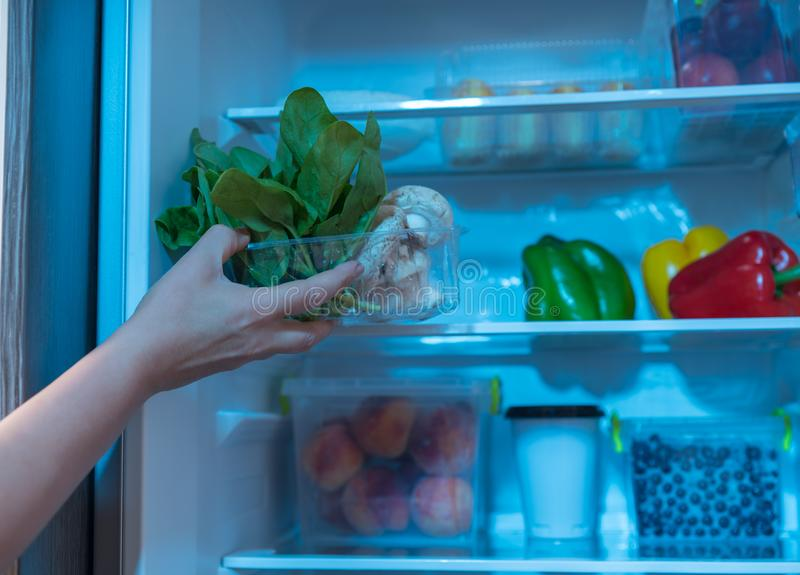 Hand reaching for bowl with spinach in fridge. Person reaching for bowl with fresh spinach in refrigerator stock photos
