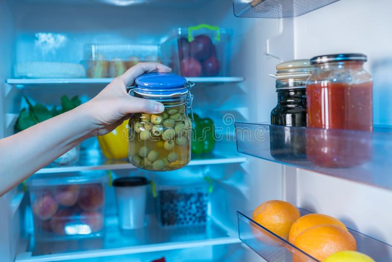 Hand reaching for jar with olives in fridge. Person reaching for jar with green olives in full refrigerator royalty free stock images