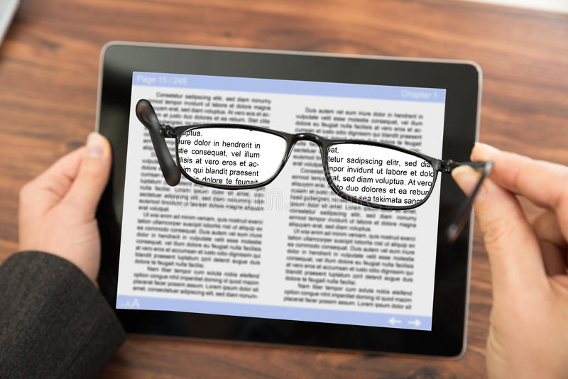 Person reading e-book with spectacles royalty free stock images