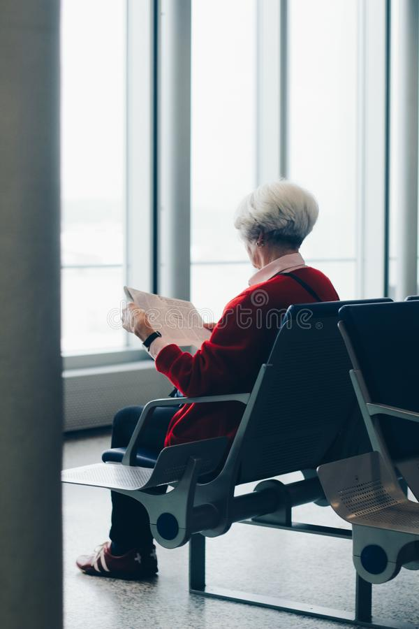 Person In Red Coat Sitting On Chair stock photo