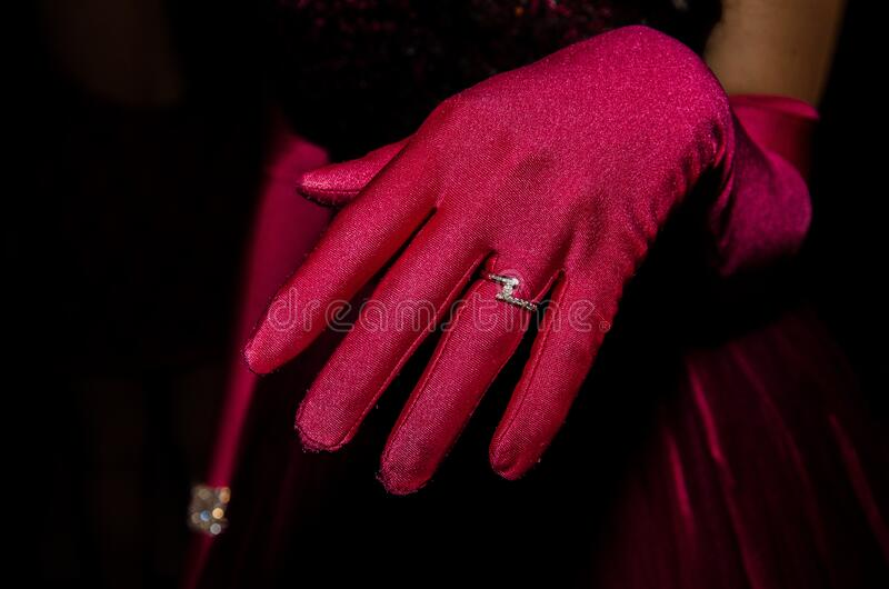 Person in Red Glove With Silver Ring royalty free stock images