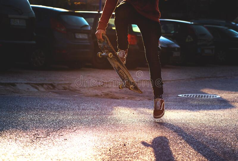 Person in Red Long Sleeved Shirt and Black Skinny Pants Riding a Skateboard stock photography