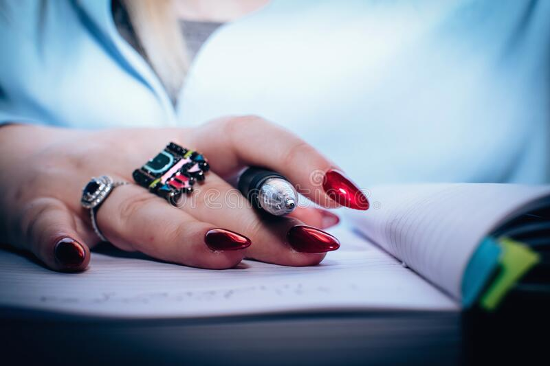 Person With Red Nail Polish Holding Black Pen royalty free stock photos