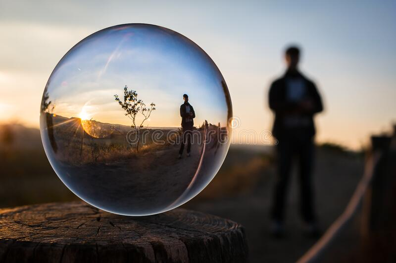 Person reflected in ball at sunset stock photo