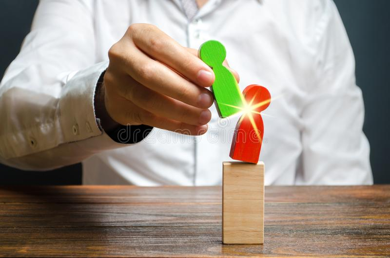 A person replaces a red human figure with a green one. firing staff. Business optimization, replacement of key employees. With loyal ones. Change of power. Anti royalty free stock photography