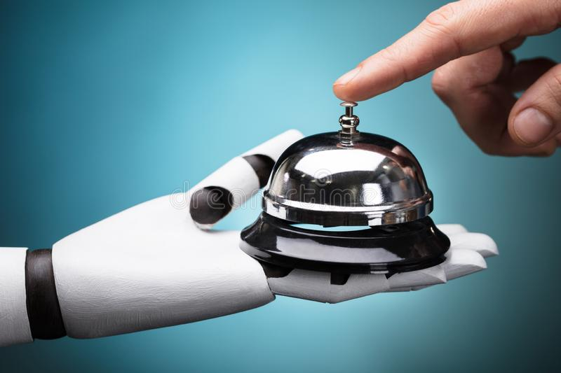 Person Ringing Service Bell Hold By Robot stock image