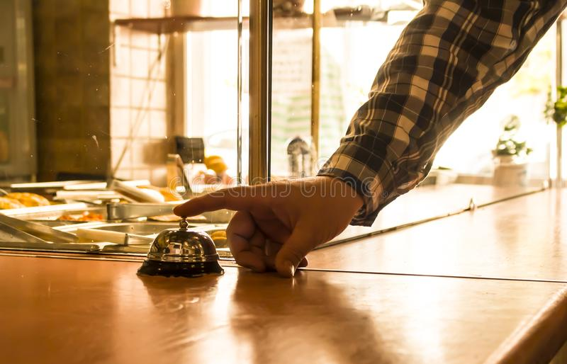 Person rings the bell at the counter in the cafe stock photo