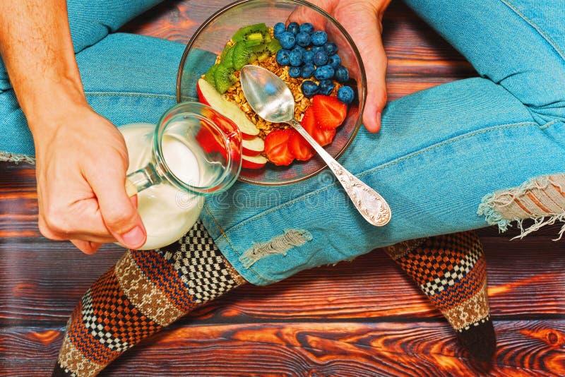 Person having healthy breakfast on wooden floor royalty free stock image